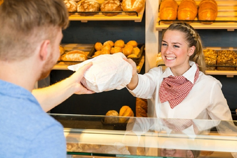 shopkeeper-in-bakery-hand-bag-of-bread-to-customer